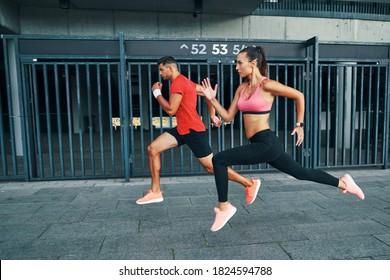 Complète longueur de deux athlètes en vêtements de sport flottant en saut en longueur tout en s'entraînant à l'extérieur