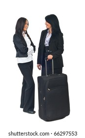 Full length of two beautiful business women with luggage having conversation before trip and smiling together isolated on white background