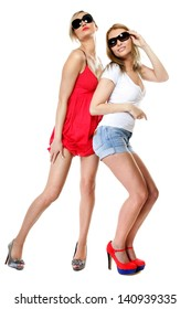 Full length two beautiful sexy crazy women in summer clothes and sunglasses. Studio portrait isolated on white background.