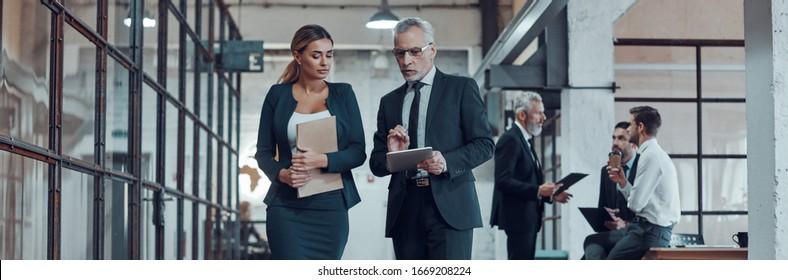 Complet de deux collègues en vêtements de sport élégants discutant des affaires en marchant dans la salle de bureau
