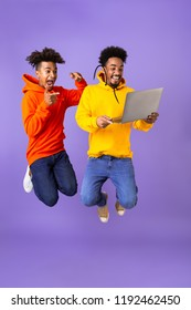 Full length of two excited male african friends in colorful hoodies jumping isolated over violet background, holding laptop computer
