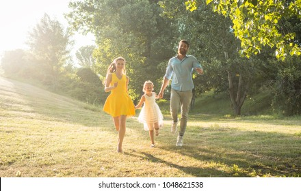 Full length of two happy parents with a healthy lifestyle, wearing casual clothes while running together with their cute daughter in a sunny day of summer