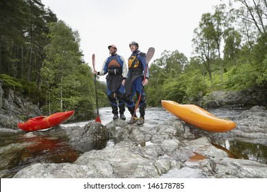 Full length of two men with kayaks by the river