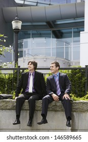 Full length of two young businessmen sitting on wall outside office
