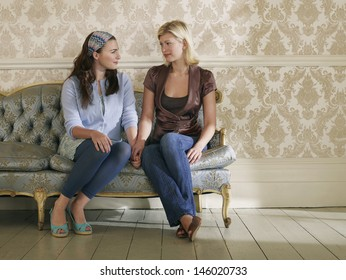Full Length Of Two Young Women Sitting On Sofa Against Wallpaper
