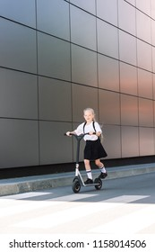 full length view of adorable schoolchild riding scooter and smiling at camera in street