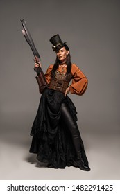 full length view of attractive steampunk woman in top hat holding gun and standing with hand on hip on grey