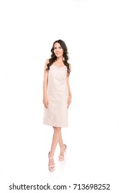 full length view of beautiful brunette woman in pink dress smiling at camera isolated on white
