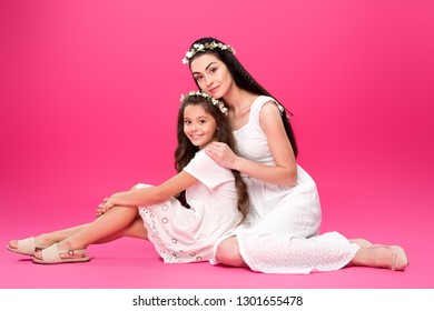 99ae3627f4 full length view of beautiful happy mother and daughter in white dresses  and floral wreaths sitting