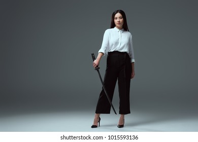 full length view of beautiful young asian woman holding katana and looking at camera on grey