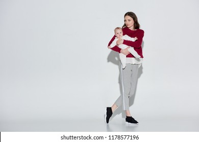 full length view of beautiful young mother in stylish outfit carrying adorable infant daughter on grey