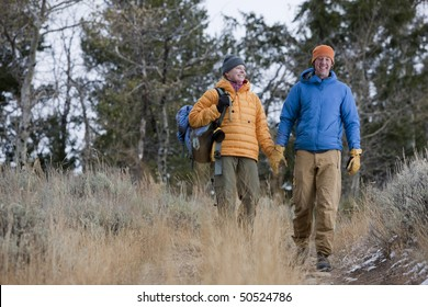 Full length view of a couple dressed in winter clothing and hiking through a wooded area. They are both smiling and walking toward the camera. Horizontal format.