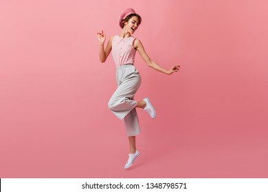 Full length view of dancing caucasian lady in pants. Refined french girl in beret having fun on pink background.