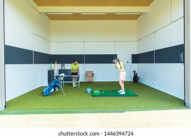Full length view of a dedicated golf coach using modern equipment, while teaching a young woman the correct movement for striking the ball as a professional player