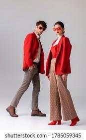 Panoramablick auf modische Paare in roten Blazer und Sonnenbrille, bei der Kamera auf Grau