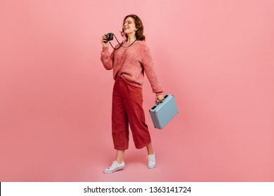 Full length view of female tourist with camera. Studio shot of amazed woman holding blue valise.