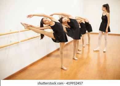 Full length view of a group of girls stretching on a barre during a ballet lesson for dance class