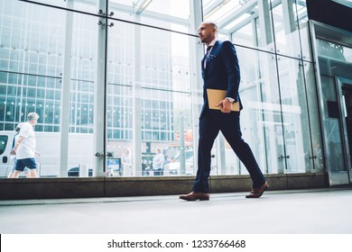 Full length view of handsome young male entrepreneur in suit passing modern office building with glass facade, confident businessman in corporate suit walking with folder in city downtown of Manhattan