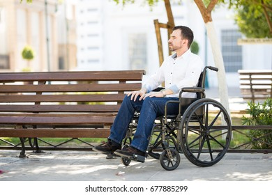 Full length view of a handsome young man sitting on a wheelchair and relaxing in the park in the morning