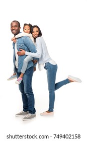 full length view of happy african american family hugging and smiling at camera isolated on white