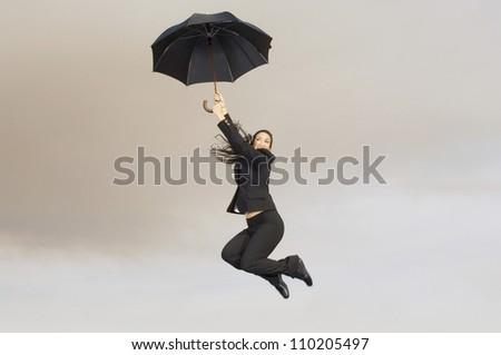 full length view of a happy businesswoman with an umbrella in midair