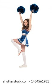 full length view of happy cheerleader girl in blue uniform dancing with pompoms isolated on white