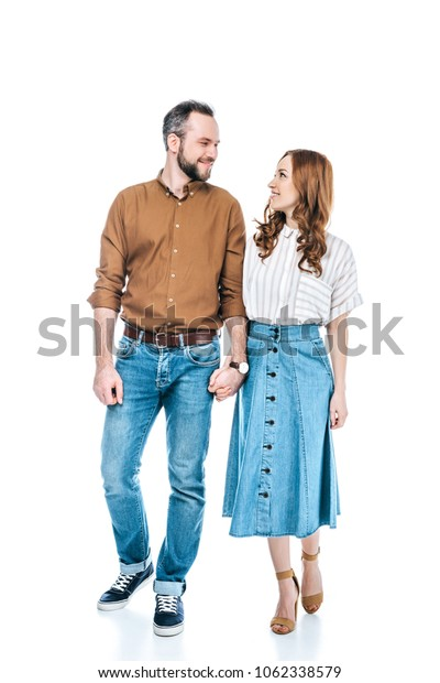 full length view of happy couple holding hands and smiling each other isolated on white