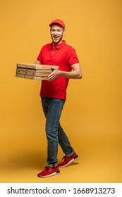 full length view of happy delivery man in red uniform walking with pizza boxes on yellow