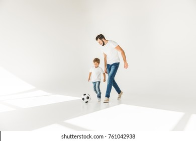 full length view of happy father and son playing together with soccer ball on white