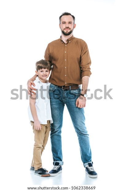 full length view of happy father and son standing together and smiling at camera isolated on white