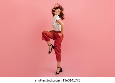Full length view of joyful woman standing on one leg. Studio shot of wonderful short-haired girl dancing on pink background.