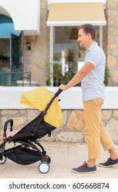 Full length view of joyful young man walking with baby stroller