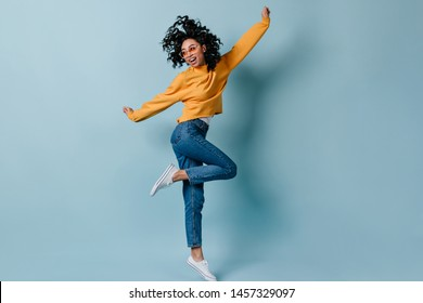 Full length view of jumping fascinating girl. Studio shot of attractive woman in jeans and yellow sweatshirt.