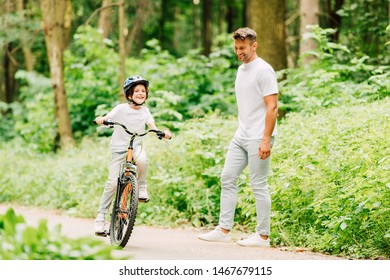 full length view of kid riding bicycle while father standing near and looking at son