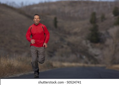 Full length view of a man running toward the camera on a country road. Horizontal format.