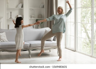 Full length view in modern light cozy living room having fun different age generation women, 60s grandmother hold hand little active granddaughter dancing enjoy life at active weekend at home concept