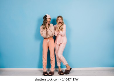 Full length view of positive girls in pajamas smiling at camera. Studio shot of pretty ladies in sleepwear standing on blue background.