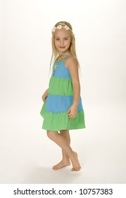 Full length view of pretty five year old girl standing in summer dress. White background.