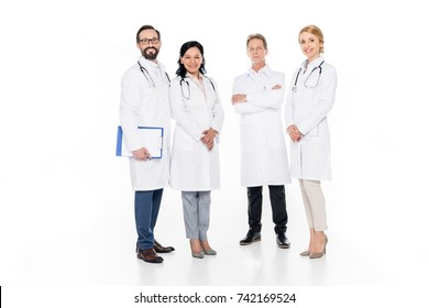 full length view of professional male and female doctors smiling at camera isolated on white