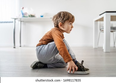 Full length view of small cute caucasian boy little child kid sitting on the wooden or laminated vinyl floor at home putting on or taking off the shoes in day alone side view