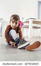 Full length view of small cute caucasian boy little child kid sitting on the wooden or laminated vinyl floor at home putting on or taking off the shoes in day alone front view
