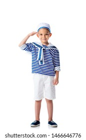 full length view of smiling preschooler child in sailor costume saluting and looking at camera isolated on white