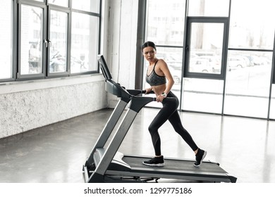 full length view of sporty young woman exercising on treadmill in gym