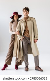 full length view of stylish woman in hat touching hand of trendy man in trench coat on grey