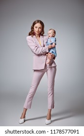 full length view of stylish young mother holding adorable infant daughter and looking at camera on grey