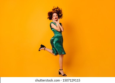 Full length view of surprised woman in green dress. Charming ginger girl jumping on yellow background.
