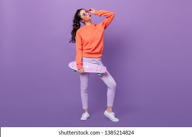 Full length view of trendy korean girl with skateboard. Studio shot of gorgeous asian woman holding longboard on purple background.