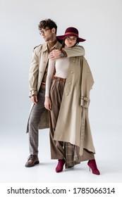 グレイの上に秋の服を着てポーズをとりながら、流行の男性がおしゃれな女性を抱き締める姿の全長にわたる眺め