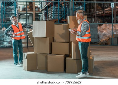 full length view of two male workers with digital tablet working with boxes in warehouse