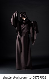 full length view of woman in death costume on black
